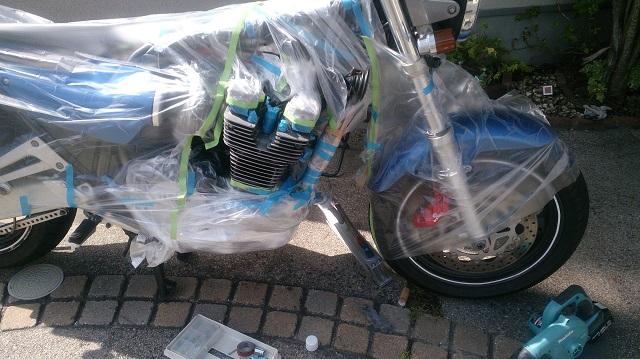 バイクにエンジンを載せたまま自家塗装するため養生をしている様子